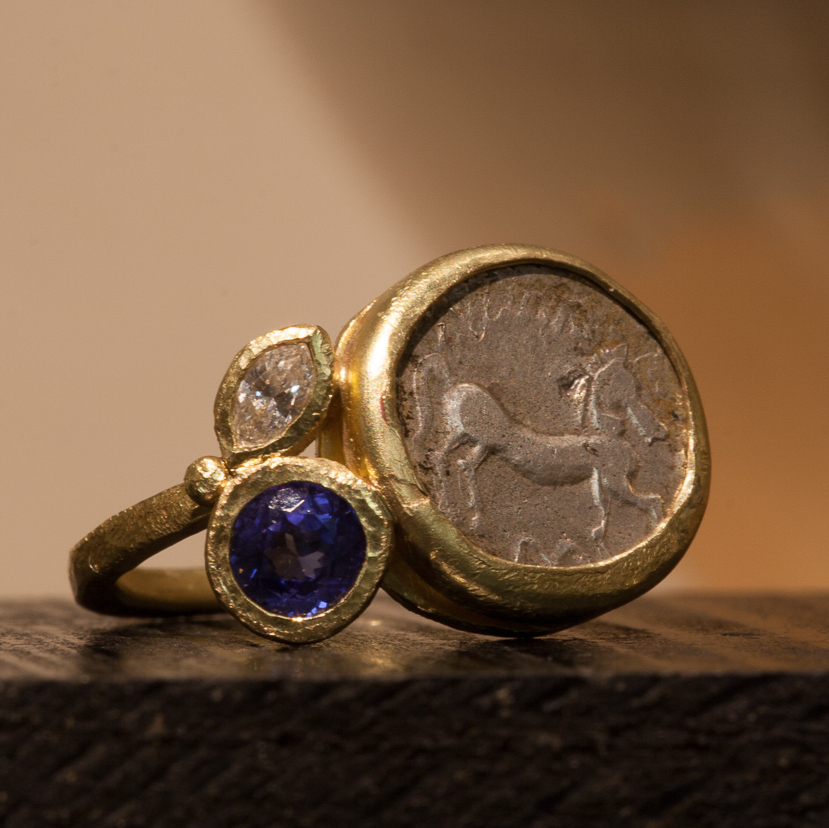 Anello con moneta celtica, brillante e tanzanite.